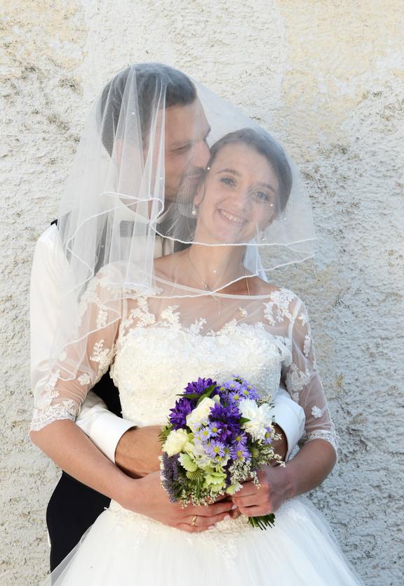 Glückliches junges Ehepaar mit Brautstrauss