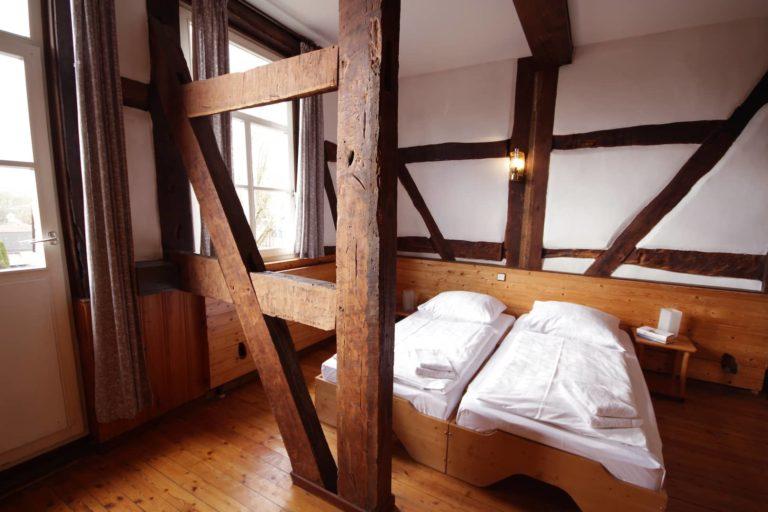 Blick auf die Schlafgelegenheiten und die offenen Balken, Apartment 32 - Teil der FeWo Fuchs