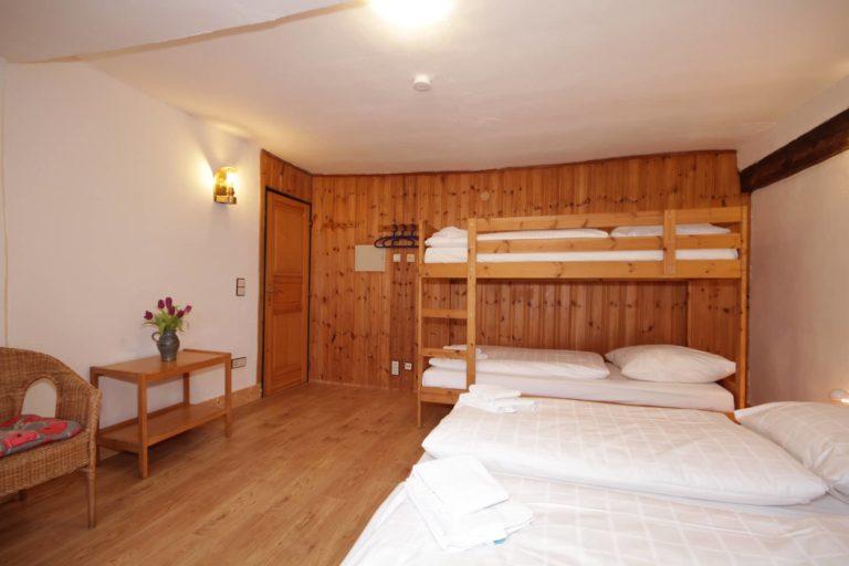 4-Bett Zimmer mit 2 Einzel- und einem Etagenbett in Apartment 61 der FeWo Amsel; Blick in den Raum